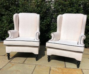 A pair of old winged arm chairs recovered in a Linwood fabric - with contrast black piping detail