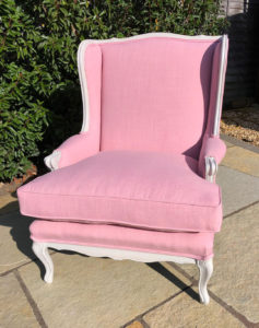 American winged back chair recovered in pink linen with new fibre filled seat cushion