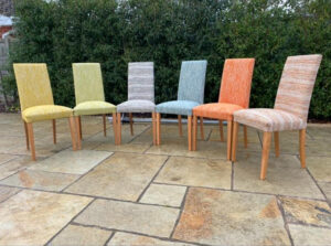 A set of dining chairs, each covered in a different fabric