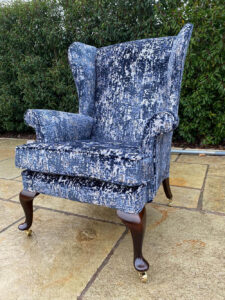 A Parker Knoll winged arm chair recovered with a new cushion, and legs recoloured