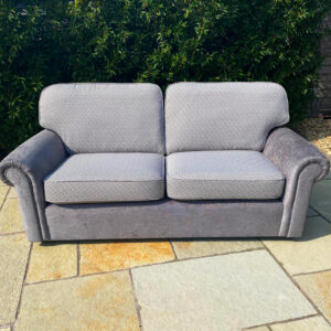 A 3 seater settee recovered in plain and patterned fabric with new cushions