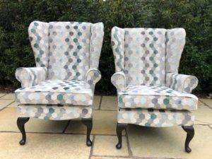 Before and after of two winged back arm chairs recovered and reupholstered in geometric design fabric