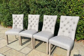 A set of button back dining chairs recovered in a faux linen